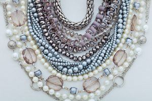 Assortment of different necklaces silver jewelry and pearls.